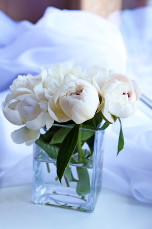 Beautiful white peonies in vase on fabric background