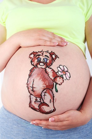 Body art on belly of pregnant woman on light background Stock Photo