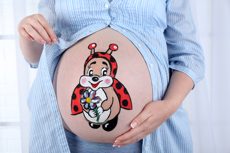 Body art on belly of pregnant woman on light background Foto de archivo