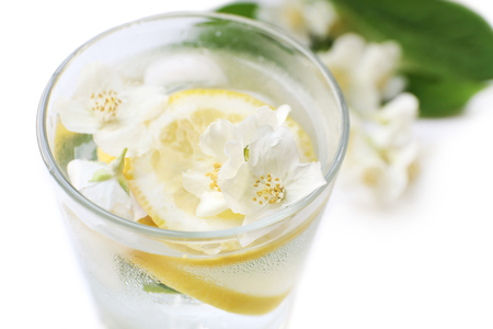 Glass of cold refreshing summer drink with flowers and slices of lemon on table close up