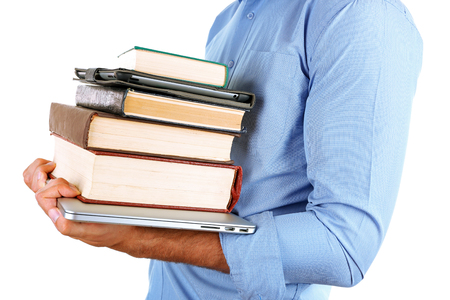 Man holding stack of books with laptop and tablet close up