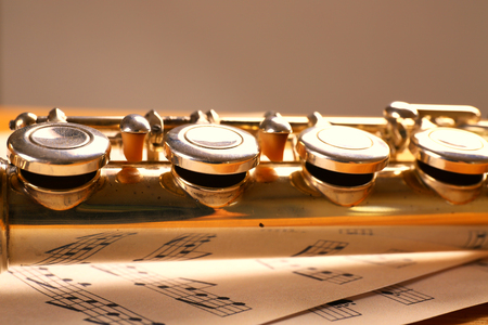 Silver flute with music notes on gray background Stock Photo