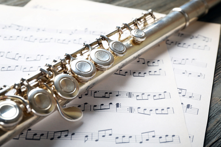 Silver flute with music notes on wooden table close up Stok Fotoğraf