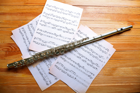 Silver flute with music notes on wooden table close up Stock Photo