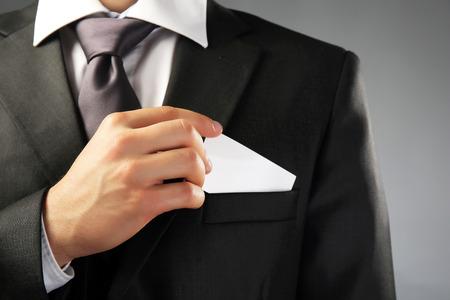 Handsome businessman holding business card close up