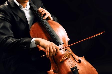 Hombre tocando el violonchelo sobre fondo oscuro Foto de archivo