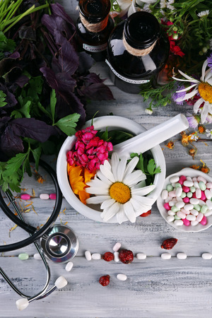 Alternative medicine herbs, berries and stethoscope on wooden table background 写真素材