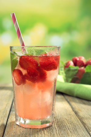 Glass of strawberry juice with berries on bright background