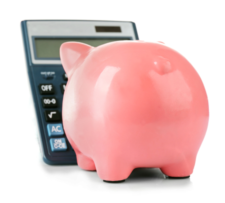 Piggy bank with calculator isolated on white Stock Photo
