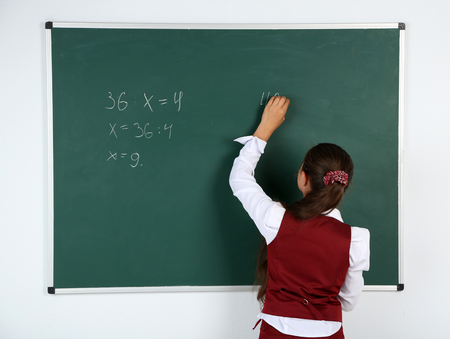 Beautiful little girl writes on blackboard in classroom Imagens