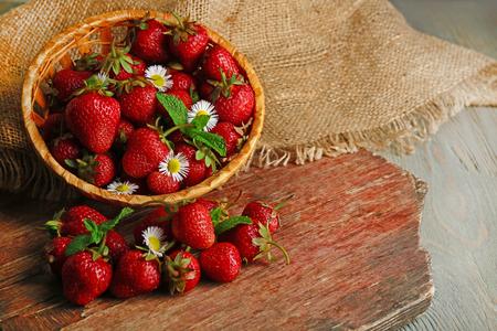 Red ripe strawberries in wicker basket, on wooden background