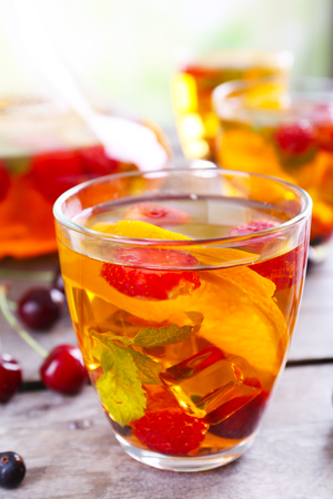 Punch with berries in glassware on wooden table, closeup Stock Photo
