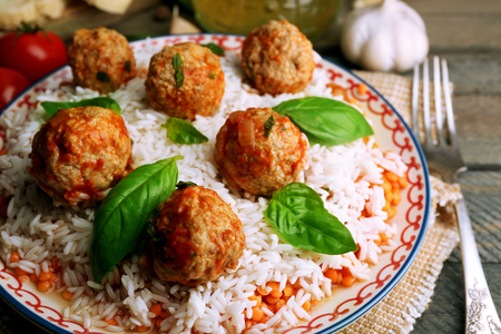 Meat balls in tomato sauce with boiled rice and lentil, wooden spoon on wooden background Stockfoto