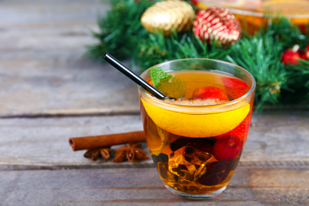 Sangria in bowl and glass with Christmas decoration on wooden table close up