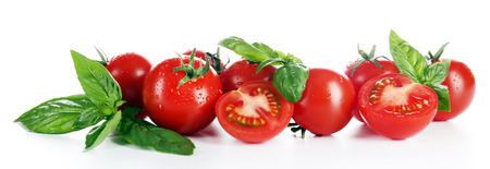 Cherry tomatoes with basil isolated on white Фото со стока