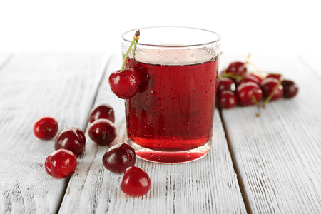 Glass of fresh juice with cherries on wooden table close up Banque d'images