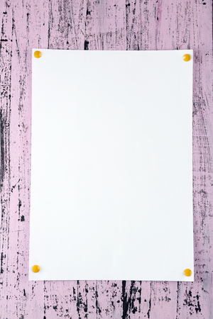 White sheet of paper attached on purple wooden background