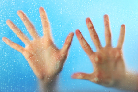 Female hands behind  wet glass, close-up Stock Photo