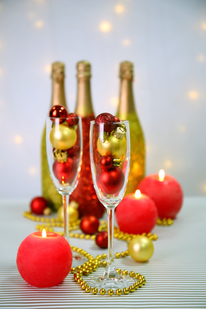 Decorative champagne bottles with beads and Christmas balls on light background