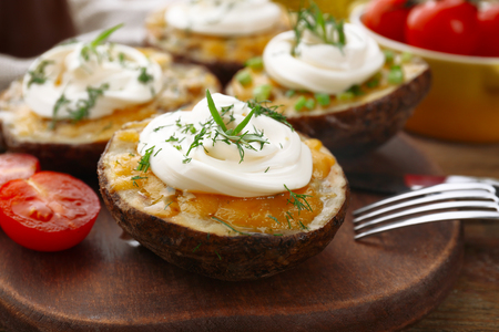 Baked potato with mayonnaise and herbs on wooden cutting board, closeup Stock Photo
