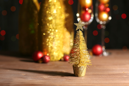 Decorative champagne bottles with Christmas balls on dark background