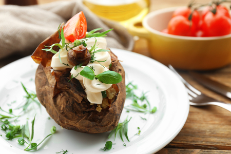 Baked potato mayonnaise herbs in white plate on wooden table, closeup