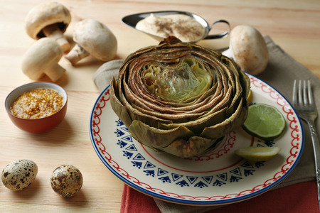Boiled artichokes on plate, on color wooden background