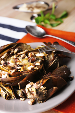 Roasted  artichokes on plate, on color wooden background