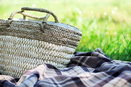 Wicker basket and Plaid for picnic on green grass Stock Photo