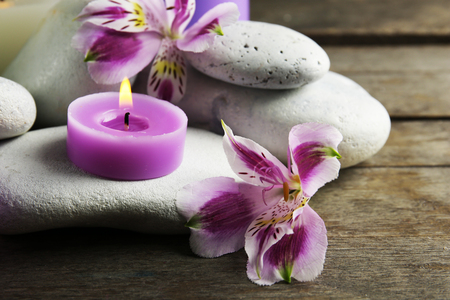Spa still life with purple flowers, pebbles and candlelight on wooden table, closeup