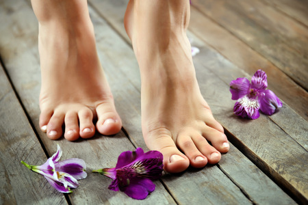 Female feet with flowers on wooden background