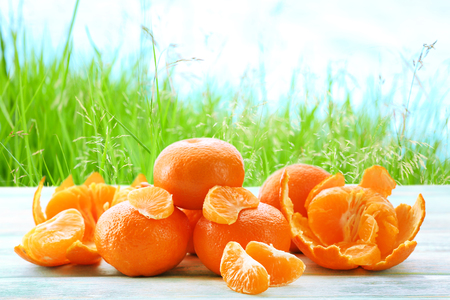 Ripe tangerines on wooden table against blurred nature background