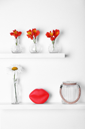 Decorative Glass Vases With Flowers On Wooden Shelf On White Stock
