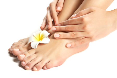 Female feet at spa pedicure procedure with plumeria isolated on white Stock Photo
