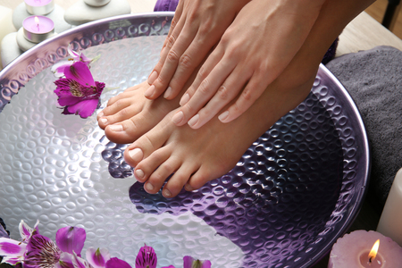 Female feet at spa pedicure procedure Standard-Bild