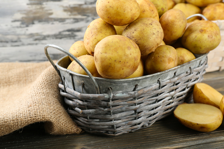 Young potatoes in wicker basket on wooden table close up