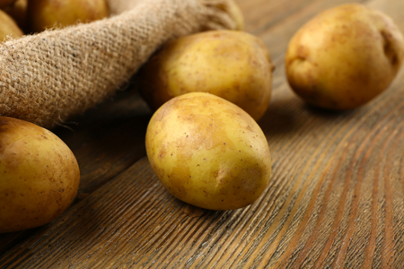 Young potatoes on wooden table close up Stock Photo