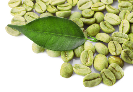 Heap of green coffee beans with leaf isolated on white Stock Photo
