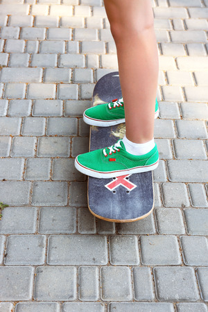 Young skateboarder in gumshoes standing on skate