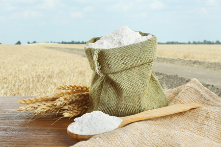 Wheat flour in burlap bag  on field background 免版税图像 - 103184594