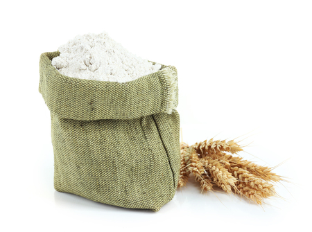 Wheat flour in burlap bag isolated on white