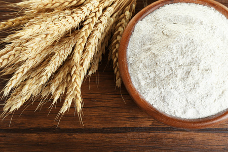 Whole flour in bowl with wheat ears on wooden table, closeup 免版税图像 - 103186603