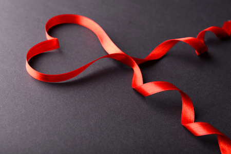 Red ribbon in shape of heart on gray background