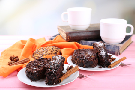 Delicious chocolate roll on wooden table with orange napkin and books ,closeup