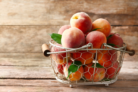 Ripe peaches in basket on wooden background 版權商用圖片 - 102100832