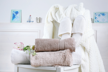 Bath set with white bathrobe on chair, indoors
