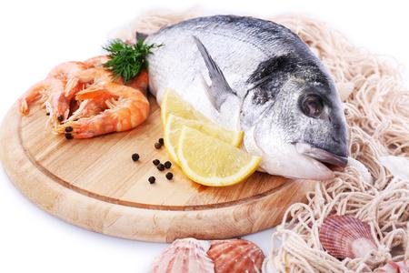 Fresh dorado fish and shrimps on wooden cutting board, closeup Stock Photo