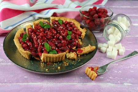 Piece of tart with raspberries on tray, close-up