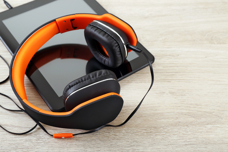 Headphones with tablet on wooden table close up Banque d'images