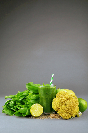 Green healthy juice with fruits and vegetables on gray background Stock Photo